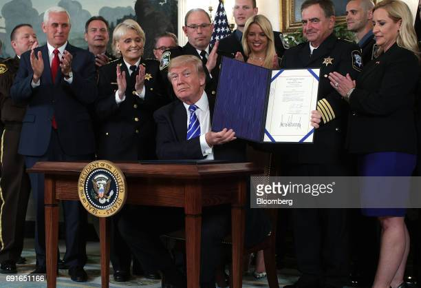 US President Donald Trump holds up signed bill S 583 the American Law Enforcement Heroes Act of 2017 as US Vice President Mike Pence left and law...
