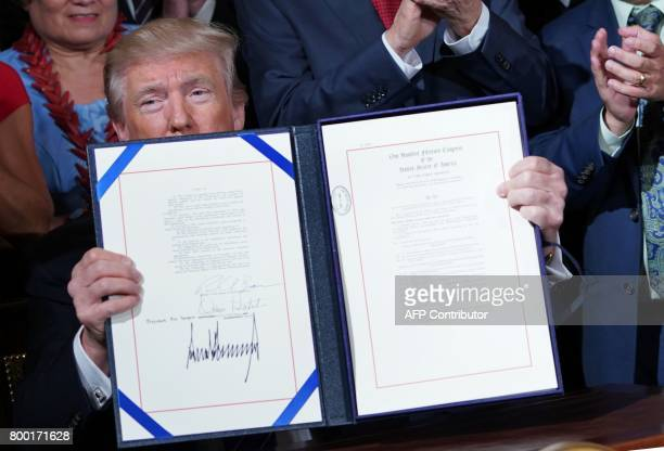US President Donald Trump holds up the Department of Veterans Affairs Accountability and Whistleblower Protection Act of 2017 after signing it at a...