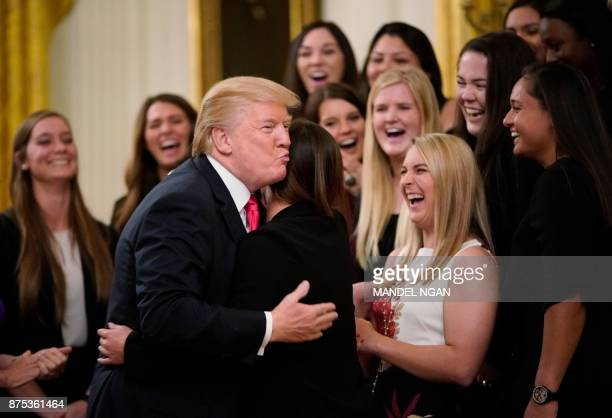 US President Donald Trump hugs a member of the Oklahoma women's softball team in the East Room of the White House during an event with NCAA national...