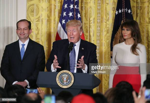 S President Donald Trump is flanked by Labor Secretary Alex Acosta and first lady Melania Trump as he speaks to guests gathered in the East Room of...