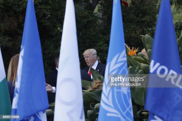 US President Donald Trump is framed by flags after a family photo with participants of the G7 summit during the Summit of the Heads of State and of...