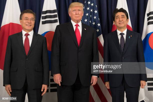 US President Donald Trump Japanese Prime Minister Shinzo Abe and South Korean President Moon Jaein pose for photos before attending the Northeast...