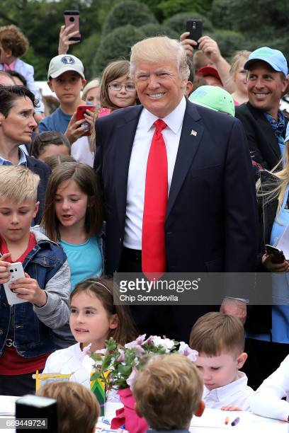 S President Donald Trump joins children at a craft table during the 139th Easter Egg Roll on the South Lawn of the White House April 17 2017 in...