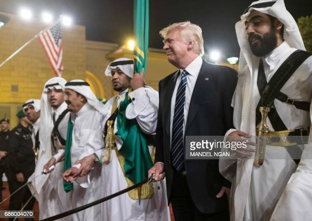US President Donald Trump joins dancers with swords at a welcome ceremony ahead of a banquet at the Murabba Palace in Riyadh on May 20 2017 / AFP...