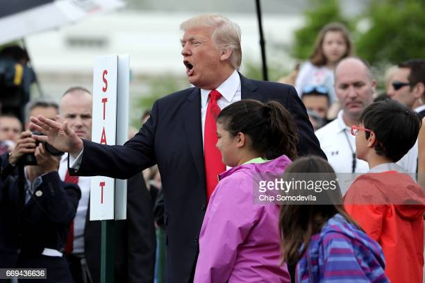 S President Donald Trump joins guests during the 139th Easter Egg Roll with Trump's daughter Tiffany Trump on the South Lawn of the White House April...
