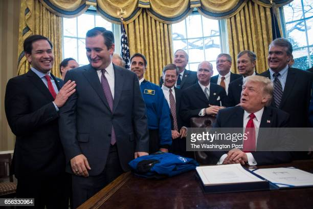 President Donald Trump jokes with Sen Marco Rubio RFla and Sen Ted Cruz RTexas after signing a bill to increase NASA's budget to $195 billion and...
