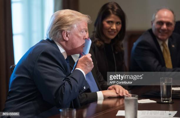 US President Donald Trump kisses a sample of the proposed new tax form as he meets with House Republican leaders and Republican members of the House...