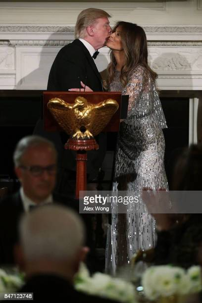 S President Donald Trump kisses first lady Melania Trump during a reception at the State Dining Room of the White House September 14 2017 in...