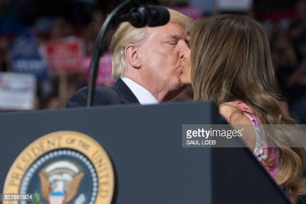 US President Donald Trump kisses First Lady Melania Trump during a Make America Great Again rally at the Covelli Centre in Youngstown Ohio July 25...