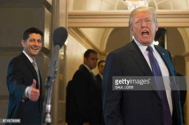 US President Donald Trump leaves alongside Speaker of the House Paul Ryan after meeting with the House Republican Conference about tax reform at the...