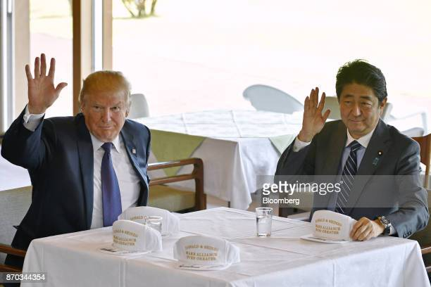 US President Donald Trump left and Shinzo Abe Japan's prime minister waves as autographed hats reading 'Donald and Shinzo Make Alliance Even Greater'...