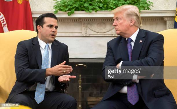President Donald Trump listens as Governor Ricardo Rossello of Puerto Rico speaks during a meeting in the Oval Office at the White House on October...