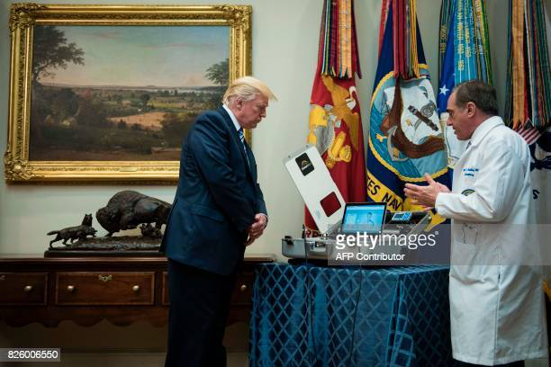 US President Donald Trump listens as US Secretary of Veterans Affairs David J Shulkin speaks about new technology used by the Department of Veterans...