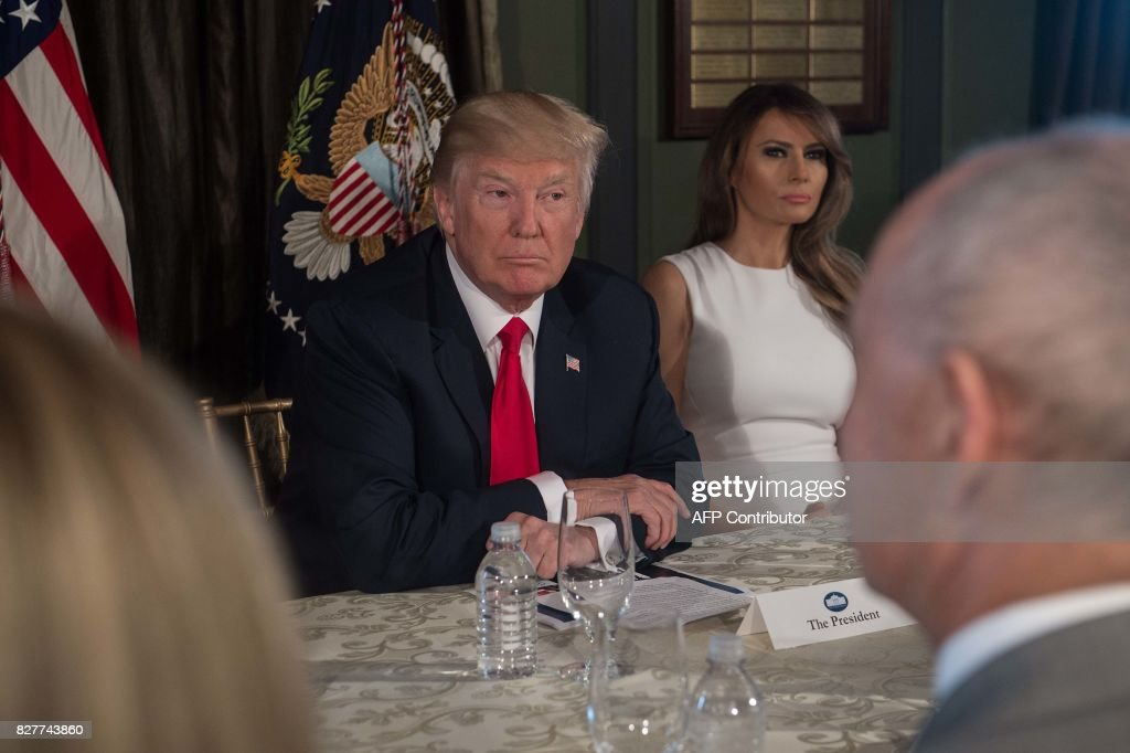 US President Donald Trump listens before a meeting with administration officials and First Lady Melania Trump (R) on the opioid addiction crisis at the Trump National Golf Club in Bedminster, New Jersey, on August 8, 2017. /