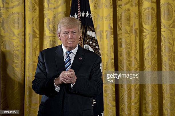 S President Donald Trump listens during a swearing in ceremony of White House senior staff in the East Room of the White House on January 22 2017 in...