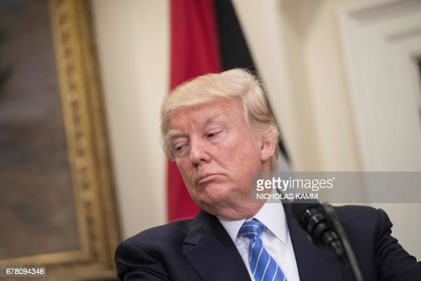 US President Donald Trump listens to Palestinian president Mahmud Abbas during a joint statement in the Roosevelt Room at the White House in...