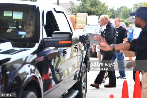 US President Donald Trump loads supplies for Hurricane Harvey victims at the First Church of Pearland on September 2 in Pearland Texas / AFP PHOTO /...