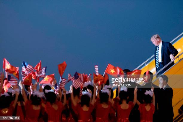 US President Donald Trump looks on a young girls wave US and Vietnamese flags as he arrives in Hanoi on November 11 2017 Trump arrived in the...