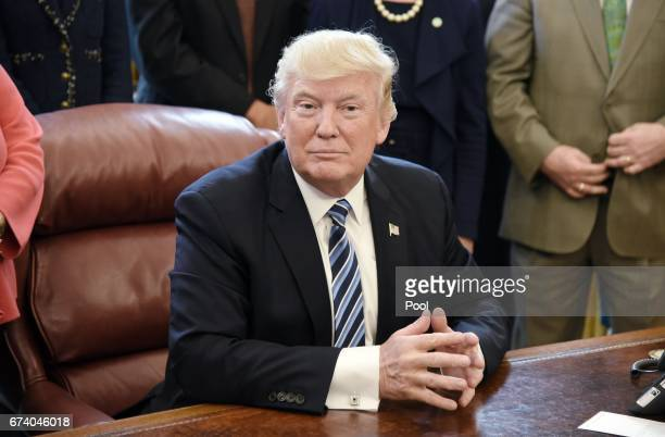 US President Donald Trump looks on after signing a Memorandum on Aluminum Imports and Threats to National Security in the Oval Office on April 27...