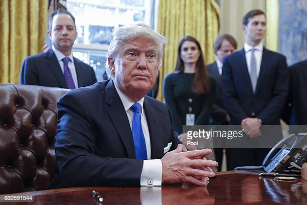 President Donald Trump looks on after signing one of five executive orders related to the oil pipeline industry in the Oval Office of the White House...