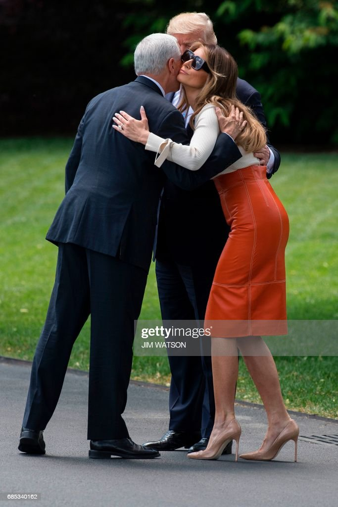 US President Donald Trump (C) looks on as First Lady Melania Trump (R) hugs Vice President Mike Pence as they leave the White House in Washington, DC, May 19, 2017. /