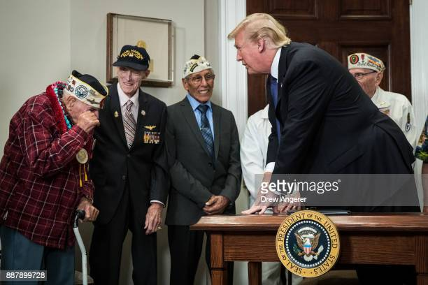 S President Donald Trump looks on as Pearl Harbor survivor Larry Parry wiped away tears after shaking hands with the President during a signing...