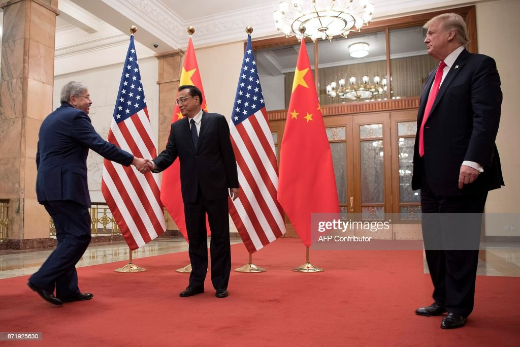 US President Donald Trump (R) looks on as US Ambassador to China Terry Branstad shakes hands with China's Premier Li Keqiang (C) in Beijing on November 9, 2017. Donald Trump urged Chinese leader Xi Jinping to work 'hard' and act fast to help resolve the North Korean nuclear crisis, during their meeting in Beijing Thursday, warning that 'time is quickly running out'. / AFP PHOTO / Jim WATSON