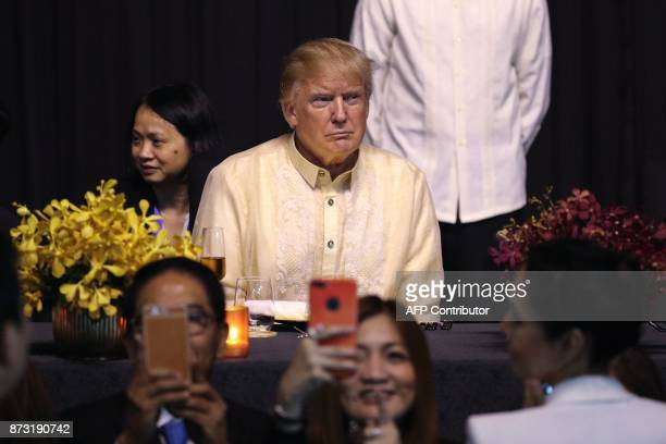 US President Donald Trump looks on during a special gala celebration dinner for the Association of Southeast Asian Nations in Manila on November 12...