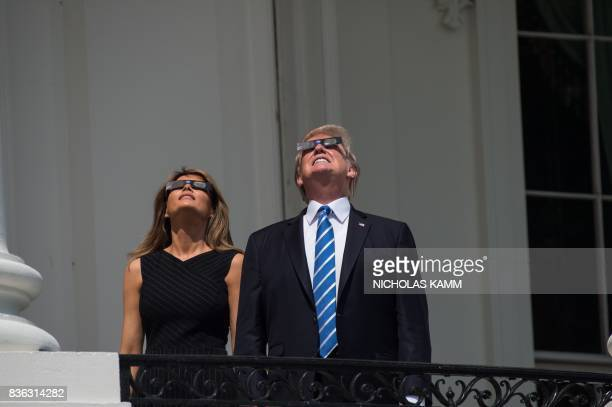 US President Donald Trump looks up a the partial solar eclipse with First Lady Melania Trump from the balcony of the White House in Washington DC on...