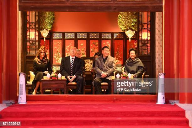 President Donald Trump looks up as he sits beside First Lady Melania Trump and China's President Xi Jinping and his wife Peng Liyuan during a tour of...