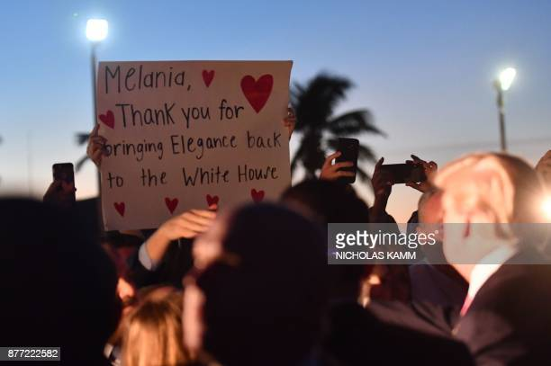 US President Donald Trump looks up at a sign from a supporter after he arrived at the Palm Beach International airport in Palm Beach Florida on...