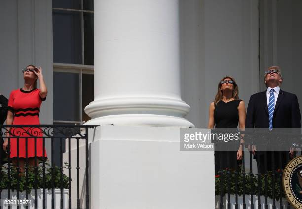 US President Donald Trump looks up at the Solar Eclipse while standing with his wife first lady Melania Trump and his daughter Ivanka Trump on the...