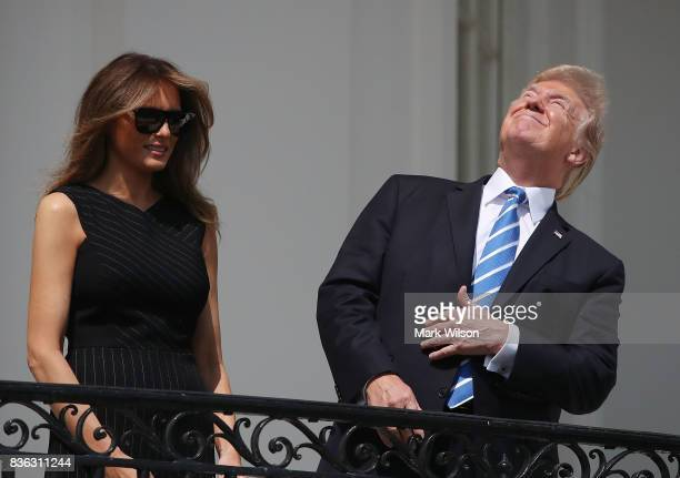 US President Donald Trump looks up toward the Solar Eclipse while joined by his wife first lady Melania Trump on the Truman Balcony at the White...