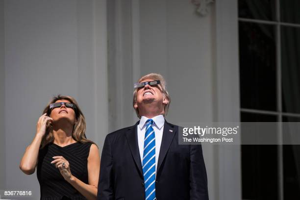 President Donald Trump looks up toward the Solar Eclipse with first lady Melania Trump by his side from a balcony at the White House in Washington DC...