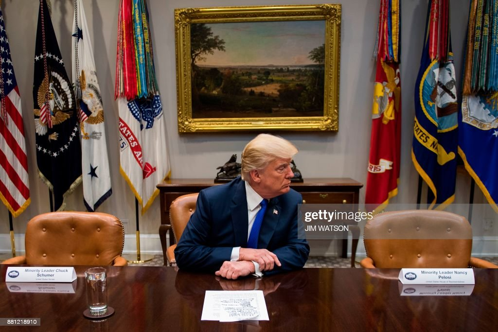 President Donald Trump (C) makes a statement from the Roosevelt Room next to the empty chairs of Senate Minority Leader Chuck Schumer (L), D-New York, and House Minority Leader Nancy Pelosi (R), D-California, after they cancelled their meeting at the White House in Washington, DC, on November 28, 2017. /