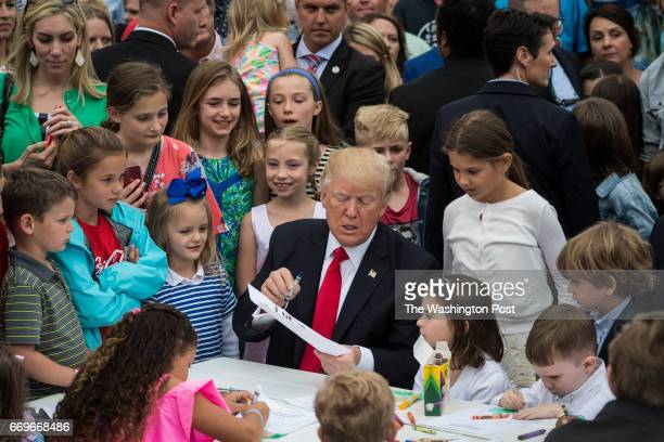 President Donald Trump makes cards for members of the military at a craft table during the 139th Easter Egg Roll on the South Lawn of the White House...
