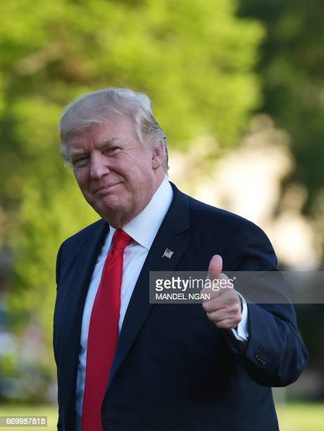 US President Donald Trump makes his way across the South Lawn upon return to the White House in Washington DC on April 18 2017 / AFP PHOTO / MANDEL...