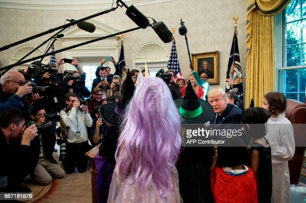 US President Donald Trump meets with children of members of the press for Halloween in the Oval Office of the White House in Washington DC on October...