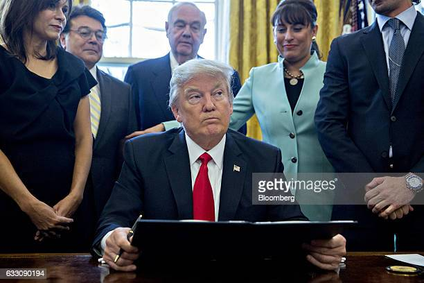 US President Donald Trump pauses after signing an executive order while surrounded by small business leaders in the Oval Office of the White House in...