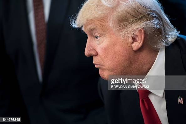 US President Donald Trump pauses before signing an executive order about regulatory reform in the Oval Office of the White House February 24 2017 in...