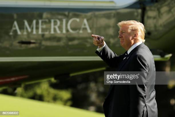 S President Donald Trump points as he walks across the South Lawn before departing the White House on Marine One October 16 2017 in Washington DC...