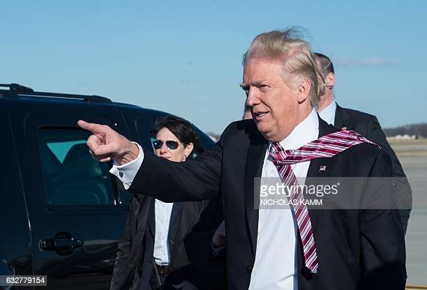 US President Donald Trump points to wellwishers after stepping off Air Force One at Andrews Air Force Base in Maryland upon his return from...