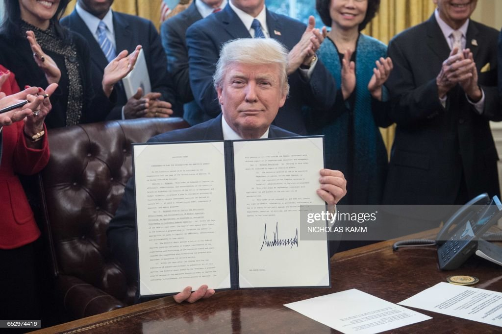 US President Donald Trump poses after signing an executive order entitled Comprehensive Plan for Reorganizing the Executive Branch in the Oval Office at the White House in Washington, DC, on March 13, 2017. /