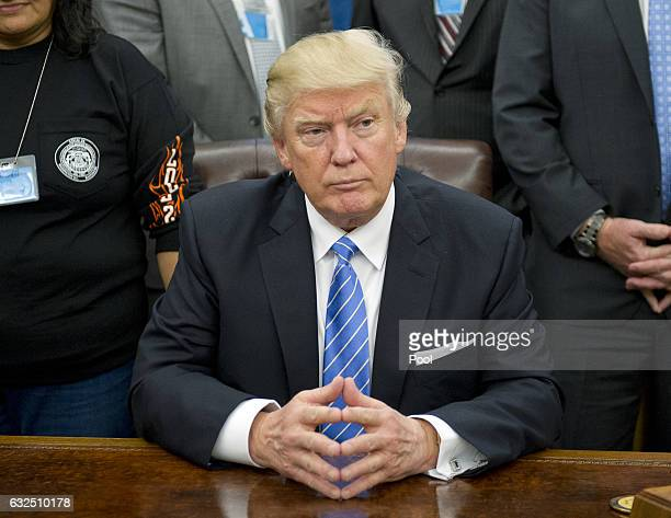 President Donald Trump poses for a group photo at a meeting with union leaders at the White House on January 23 2017 in Washington DC President Trump...