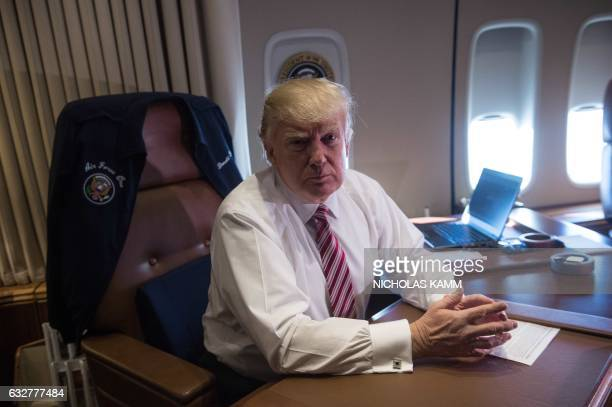 US President Donald Trump poses in his office aboard Air Force One at Andrews Air Force Base in Maryland after he returned from Philadelphia on...