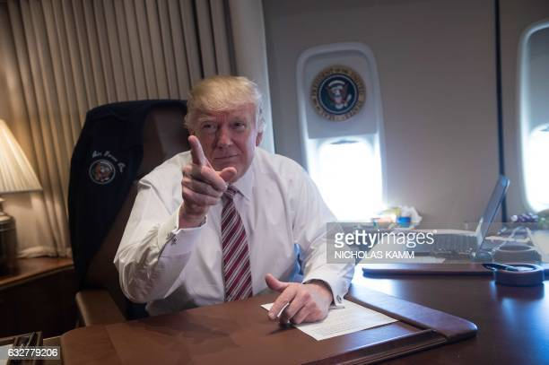 President Donald Trump poses in his office aboard Air Force One at Andrews Air Force Base in Maryland after he returned from Philadelphia on January...