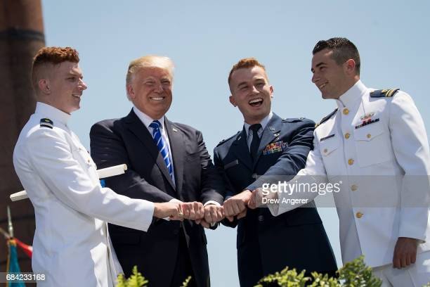 President Donald Trump poses with Coast Guard cadets as he hands out diplomas at the commencement ceremony for the US Coast Guard Academy May 17 2017...