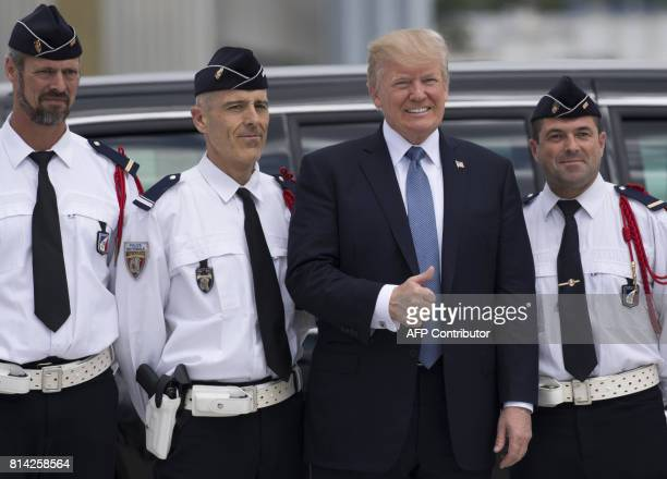 President Donald Trump poses with French Police Officers before boarding Air Force One and departing Paris Orly Airport on July 14 following a twoday...