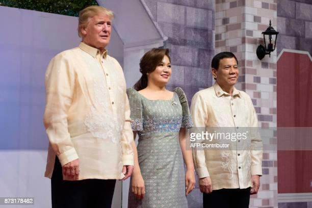 US President Donald Trump poses with Honeylet Avancena partner of Philippine President Rodrigo Duterte upon arriving for the special gala celebration...