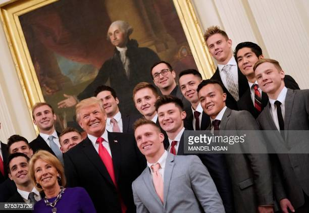 US President Donald Trump poses with members of the University of Oklahoma men's gymnastics team in the East Room of the White House during an event...